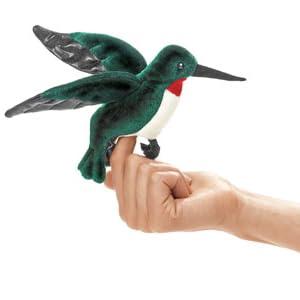 Hummingbird finger puppet posed on model's hand.