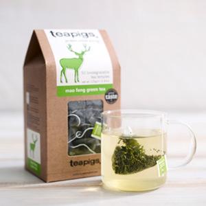 box of teapigs mao feng green tea next to a cup of tea