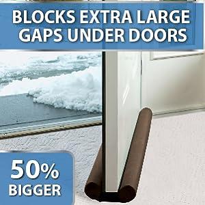 50% bigger brown Twin Draft Guard on white carpet with door open. Snowy doorstep at entry door
