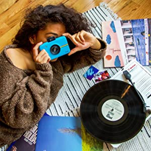 girl taking picture with blue instant camera of a old record player