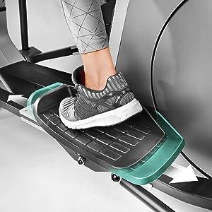 Una persona con los zapatos deportivos arriba de un crosstrainer con pedales antideslizantes.