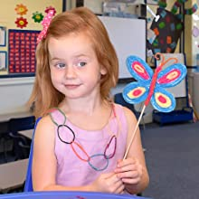 GIRL HOLDING BUTTERFLY CRAFT WEARING WIKKI NECKLACE