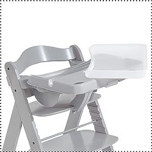 Il tavolino con bordo elevato e pratica cavità per il biberon si occupa di non lasciar niente cadere