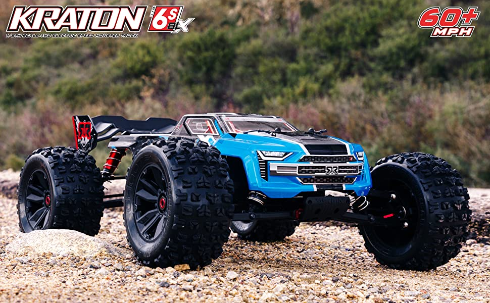 Blue ARRMA KRATON 6S BLX 1/8 RC monster truck on gravel with grassy, hilly background