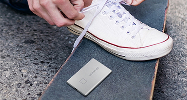 Samsung Portable SSD T7 Touch on a skateboard while someone ties their shoe
