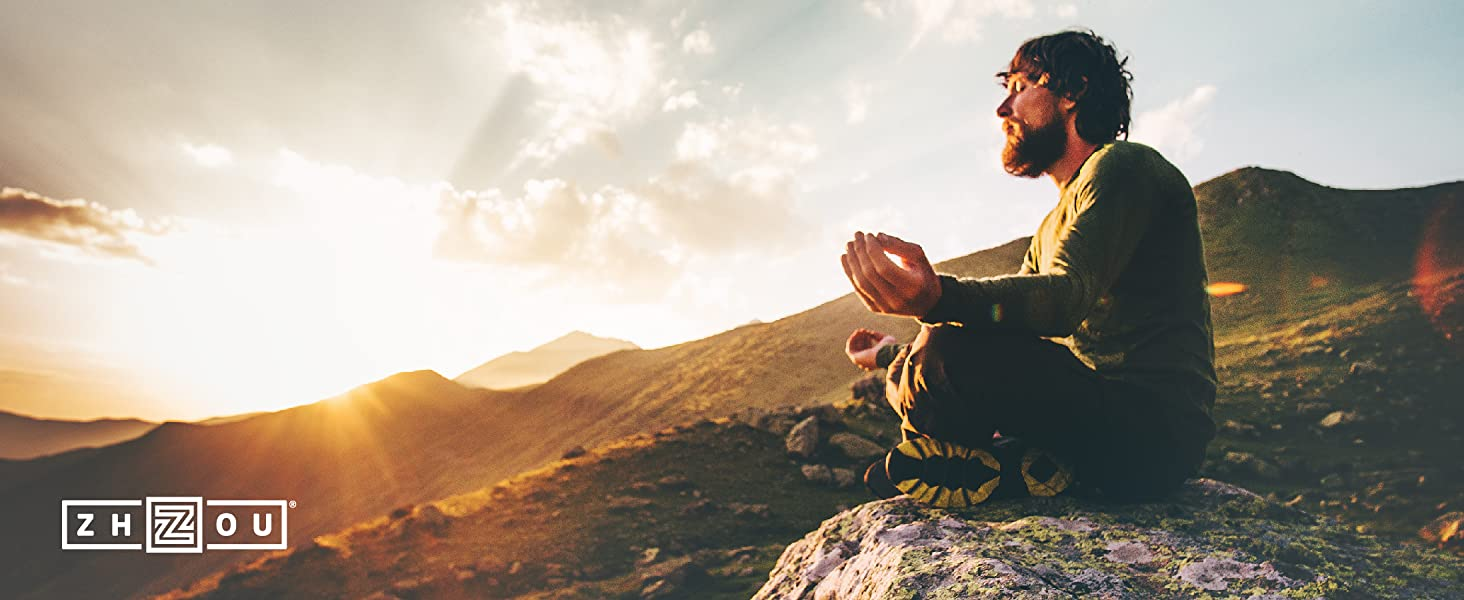 Man meditating on rock watching sun rise in mountains.
