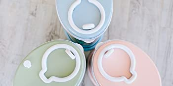 Top view of sage, cloudy blue, and blush pink Ubbi diaper pails arranged in clover-like formation