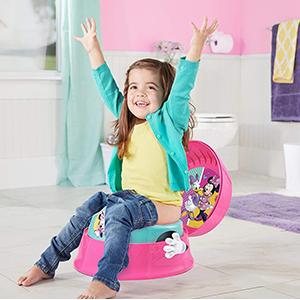 Little girl sitting using potty seat