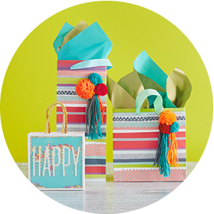 Festive birthday gift bags in teal, coral, pink, light blue and orange stripes, tassels and confetti