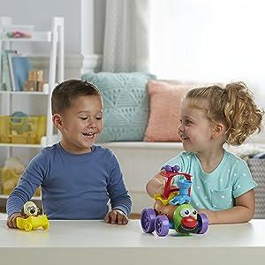 Duas crianças brincando com as figuras grande e pequena de Mr. Potato Head