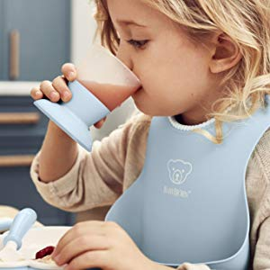 girl drinking form blue cup and wearing the blue bib