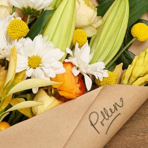 Pollen written on paper wrap around bouquet of flowers