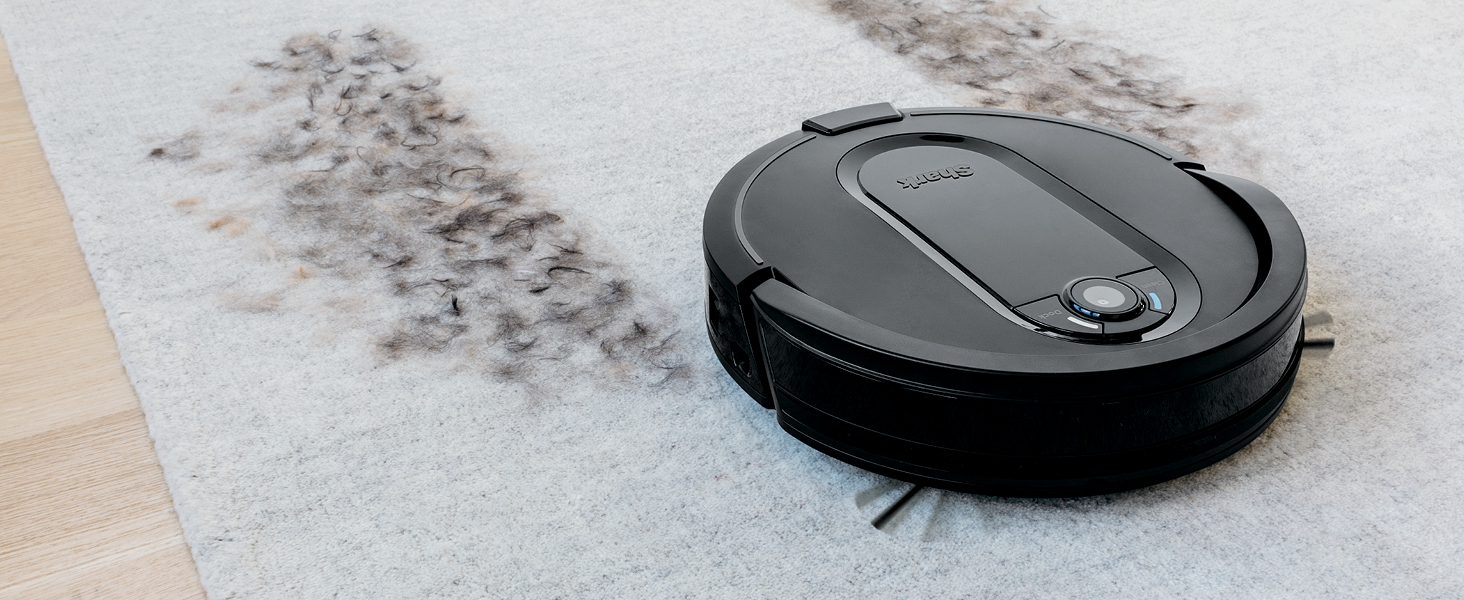 Shark IQ robot self-empty XL vacuum cleaning up feathers on a carpet