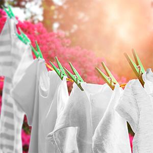 Een waslijn met vlekkeloos schone, witte t-shirts, buiten aan het drogen in de zon