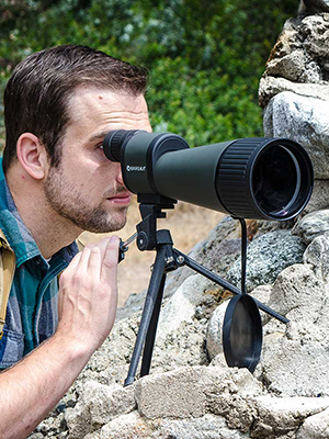 Man looking through scope in outdoor setting
