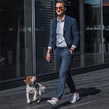 man in dress pants walking dog