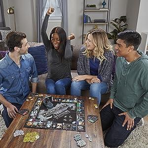 Grupo de jovens em volta da mesa, jogando o novo Monopoly Game of Thrones.