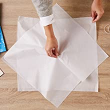 For perfectly fluffed tissue paper in gift bags, begin by pinching center of a sheet of tissue paper