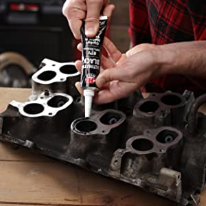 Guy using sealant to seal up an engine