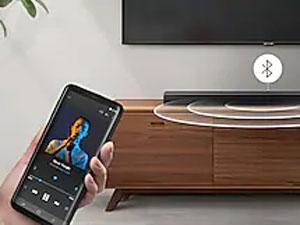Someone playing music through the Soundbar via Bluetooth