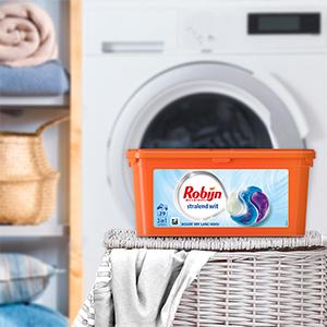 Een verpakking van de Robijn wascapules op een volle wasmand met lichte kleding voor een wasmachine