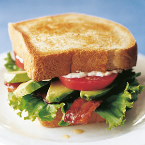 Photograph of the California BLT, a tall sandwich stacked with bacon, tomato, avocado, and lettuce