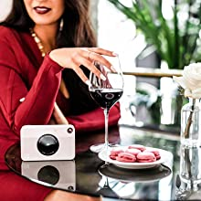 camera next to a woman in red dress sipping wine.