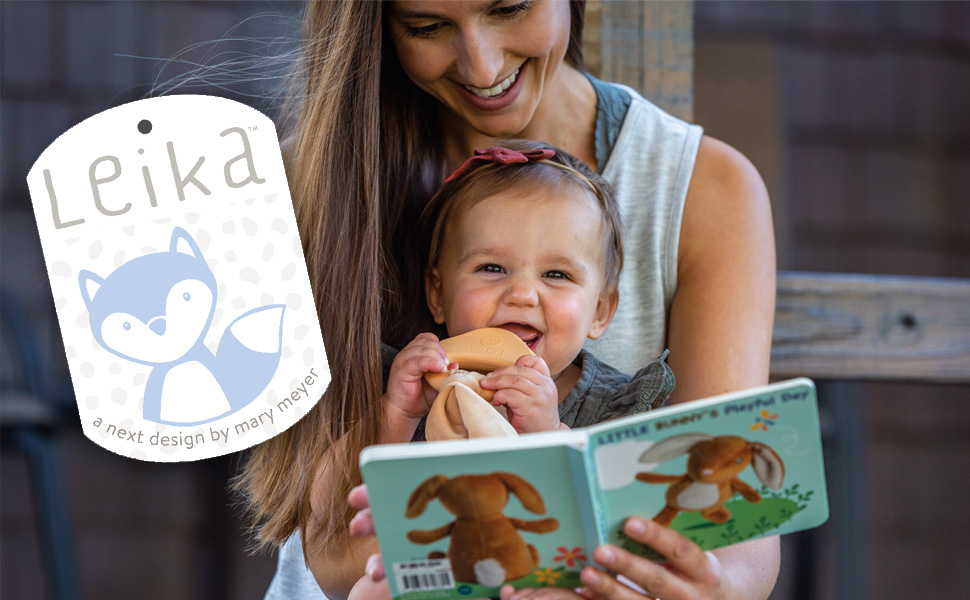 Mother and baby read a board book together while baby chews on bunny shaped teether