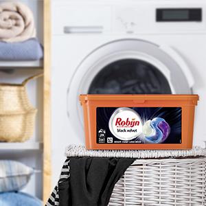 Een verpakking van de Robijn wascapules op een volle wasmand met kleding voor een wasmachine