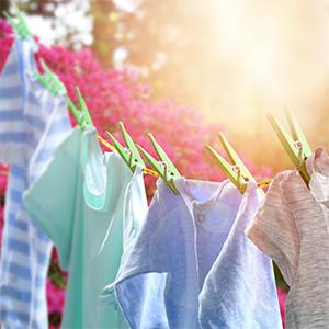 Een waslijn met vlekkeloos schone, gekleurde t-shirts, buiten aan het drogen in de zon
