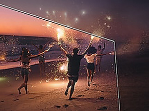 People with sparklers running down the shore on a TV screen