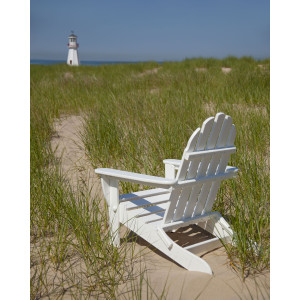 White adirondack chair placed in a sandy, grassy area, facing a lighthouse
