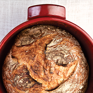 Photograph of baked bread loaf in red pan