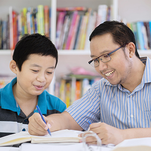 a father helping his child with work in a library