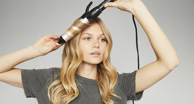 Wrap a section of hair evenly around the barrel to create a loose curl effect.