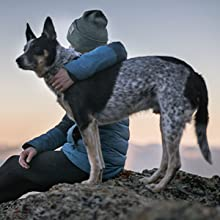 person and dog at top of a hill watching the sunset