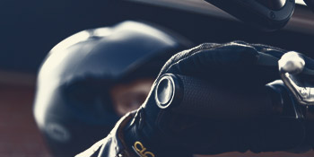 Motorcycle rider close up wearing helmet and gloves with hand around handlebar grip.