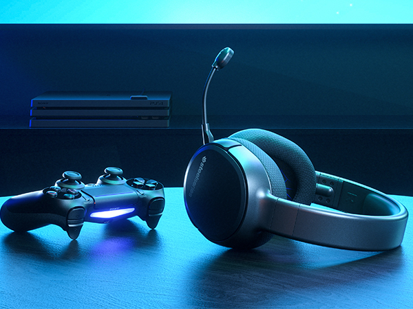 - Arctis 1 Wireless laying on a table with a controller in front of a TV