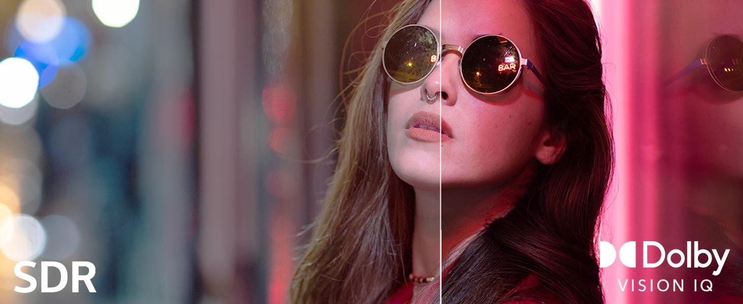 Frau mit Sonnenbrille lehnt an bunte Fensterscheibe: Unterschied Dolby Vision zu SDR
