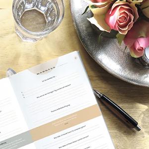 Aufgeschlagenes Buch neben einem Wasserglas und einem Blumengesteck