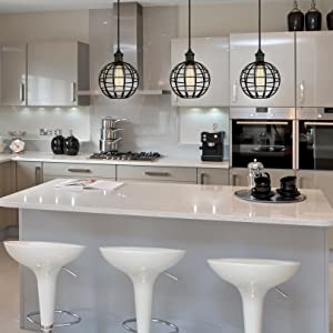 Trzy matowe czarne wisiorki do klatek wiszące na nowoczesnej białej wyspie kuchennej.