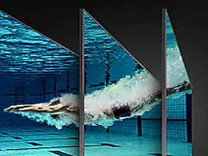 QLED TV with underwater scene of a swimmer diving into a pool from multiple angles