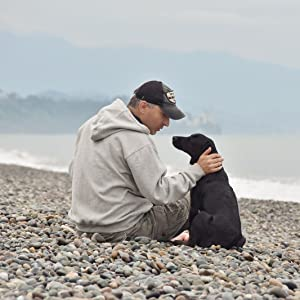 Owner sitting with his dog on a rocky beach