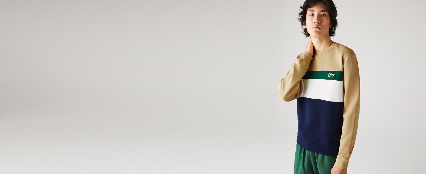 Modelo con sudadera gráfica verde, azul marino, beis y blanca.