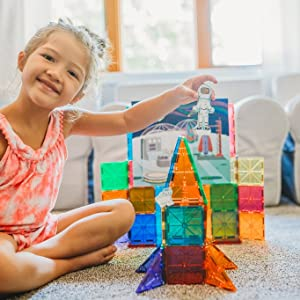 Young girl is engaging in dramatic play with Magna-Tiles