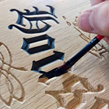This is an image showing one of our house signs being hand painted after being engraved