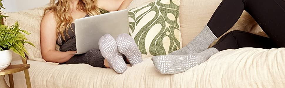 Woman on comfortable couch using laptop and with grey grip socks
