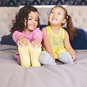 two girls on bed in yellow grey grip socks laughing smiling comfortable showing toe heel grip
