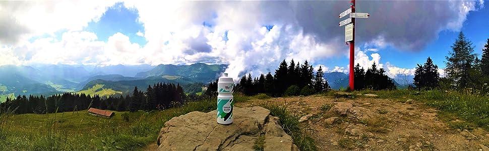 Hier steht die Wasserflasche auf einem Berg, beim Gipfelkreuz. Zu sehen ist ein schönes Panorama.