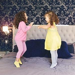 due bambine sul letto in calzini aderenti grigi gialli che ridono sorridenti confortevoli mostrando